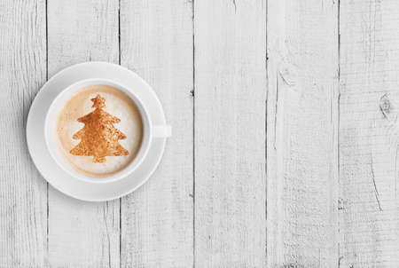 christmas drink: coffee cup with christmas tree shape on white wood table