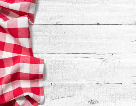 red cloth: red checked picnic tablecloth on white wooden table left side