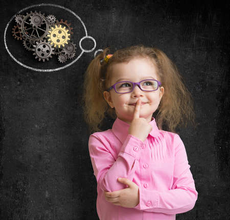 preschool teacher: kid in glasses with bright idea standing near school blackboard in classroom Stock Photo