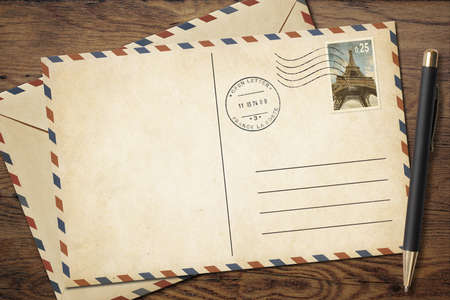par avion: Old postcard and envelope with pen on table top view