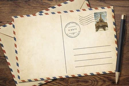 postcard: Postal antigua y el sobre con la pluma en la vista superior de la mesa