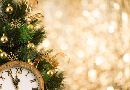 christmas gold: Christmas tree with retro clock face on gold blurred light Stock Photo