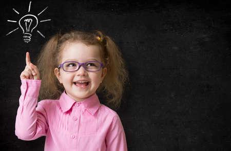 maestra preescolar: ni�o en gafas con idea l�mpara en la pizarra de la escuela en el aula Foto de archivo