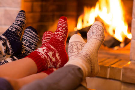 comfortable home: Feet in wool socks near fireplace in winter time