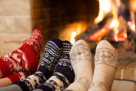 incendio casa: Pies en calcetines de lana cerca de la chimenea en invierno
