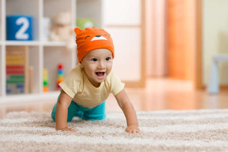baby boy at home crawling on carpet