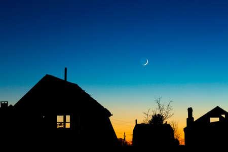 silhouette maison: Maisons toits sur le ciel de nuit avec la nouvelle lune Banque d'images