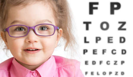 poor eyesight: Smiling girl putting on glasses with blurry eye chart behind her isolated on white