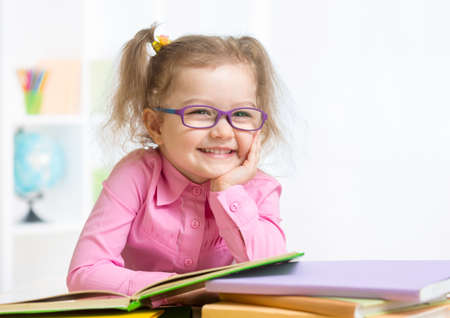 Lachend meisje draagt bril lezen van boeken in de klas Stockfoto
