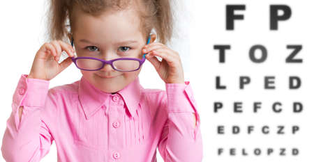 glasses eye: Funny kid putting on glasses with blurry eye chart behind her on white