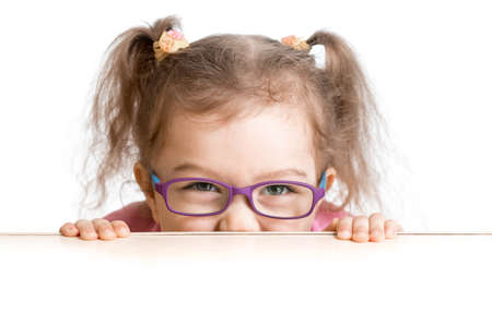 poor eyesight: frightened kid in spectacles looking from under table