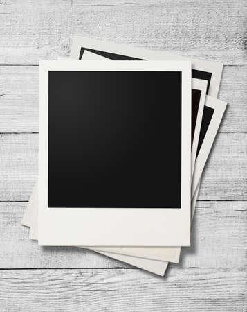 Polaroid photo frames on white old wooden background