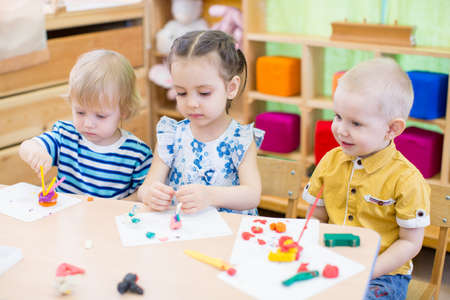 day care center: kids group learning and playing in kindergarten