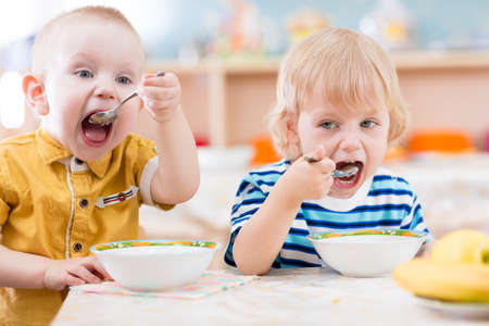 funny kids eating in kindergarten Stock Photo