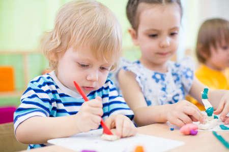 niños grupo de modelado o jugando en el jardín de infantes juntos