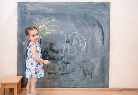 girl studying: Full length cute kid girl standing near blackboard