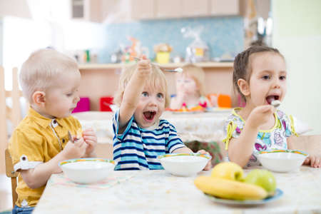 funny kids group eating in kindergarten Imagens - 56492841