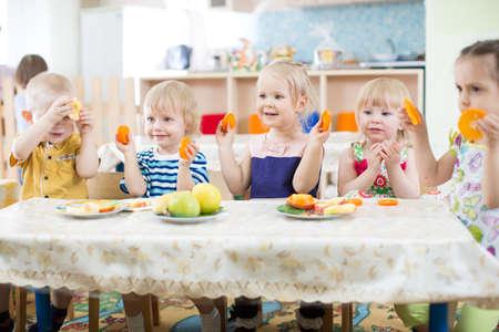 niños comiendo: niños divertidos que comen frutas en guardería Foto de archivo