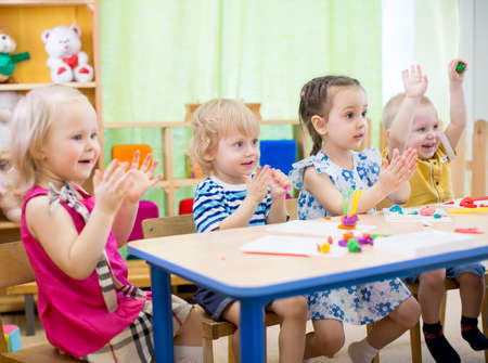clay craft: kids group learning arts and crafts in day care centre or kindergarten Stock Photo