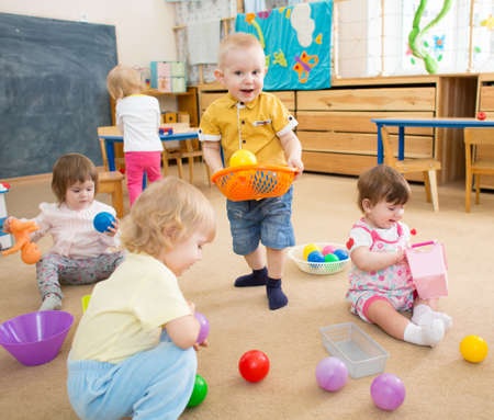 Group of kids playing with balls in kindergarten or day care centre