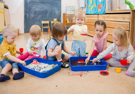 Group of children playing with rice and beans in kindergarten or day care centre
