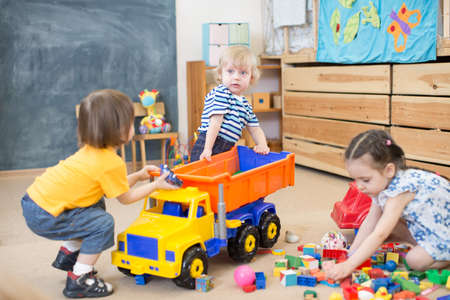 two kids pull toy truck in kindergarten play room each to his own side