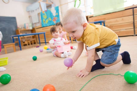 kid playing with balls in kindergarten or day care centre