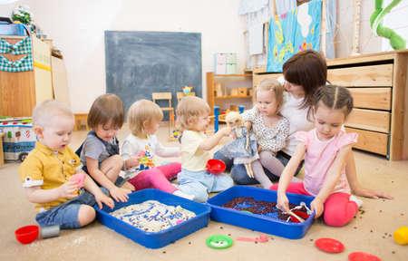 Groep kinderen en verpleegkundige spelen met rijst en bonen in de kleuterschool of crèche