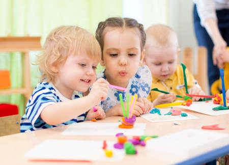 モデリングまたは興味のある幼稚園で遊んで幸せな子供たち