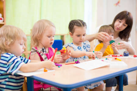 kids group learning with teacher arts and crafts in day care centre playroom Standard-Bild