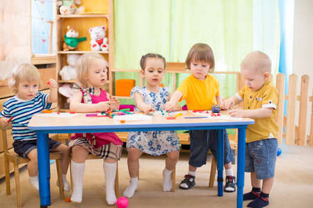 kids group learning arts and crafts in day care centre playroom
