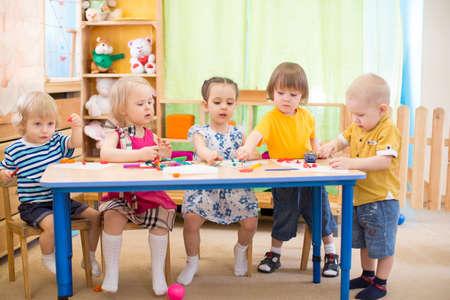 kinderen groep leren kunsten en ambachten in crèche speelkamer Stockfoto