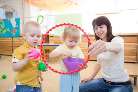 day care: Happy kids playing ball and ring in kindergarten playroom with teacher Stock Photo