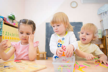 day care center: kids group playing puzzle and other board games in day care centre