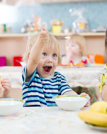 funny kid eating and playing in kindergarten