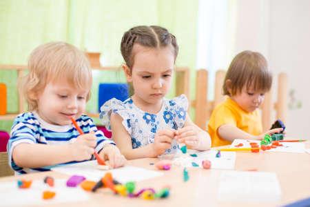 modelado grupo de niños o haciendo artes y oficios en el jardín de infantes juntos