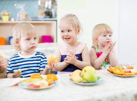 boy kid: children eating fruits in kindergarten dinning room Stock Photo