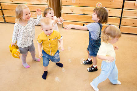 day care center: Group of children playing with soap bubbles in kindergarten