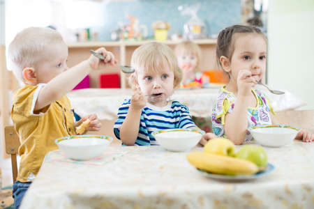 playing with spoon: funny childen eating in kindergarten
