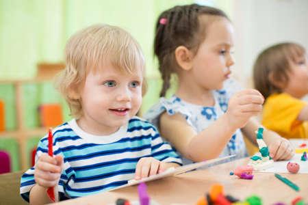children at play: children making arts and crafts in kindergarten together