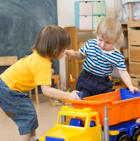 pull toy: two kids pull toy truck in kindergarten play room each to his own side