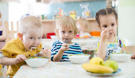 Funny children eating in day care centre