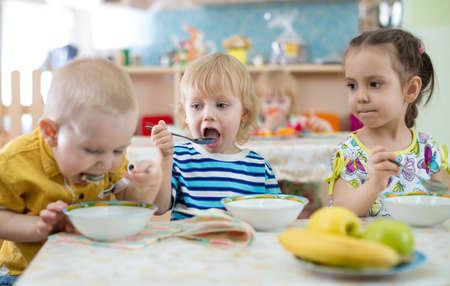 Grappig groep kinderen eten in crèche Stockfoto