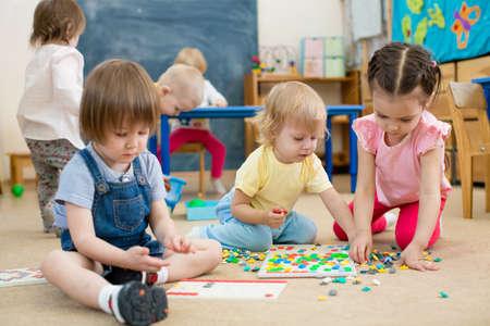 Grupa dzieci bawi mozaika gra w przedszkolu