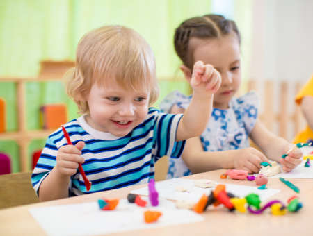 doing: Happy kids modeling or playing in kindergarten with interest. Kids in kindergarten. Stock Photo