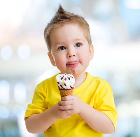 Funny child with icecream on blurred background photo