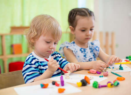 center table: Children spending time in day care centre with the great interest.