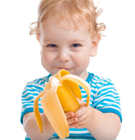 eating fruits: Happy kid or child eating banana isolated on white