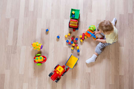 baby playing: Little blond kid boy playing with colorful car toys top view Stock Photo