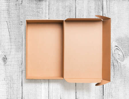 flap: Open cardboard box top view on wooden floor Stock Photo